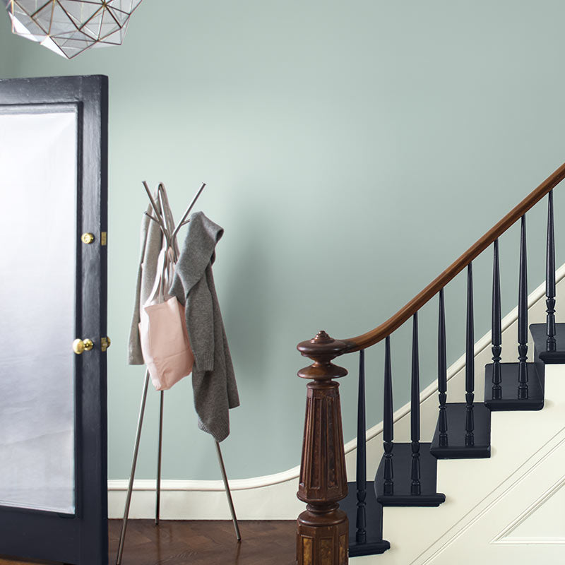 A blue-gray wall with white trim sets off a staircase with black stairs and an ornate wood banister. Color of the Year 2019