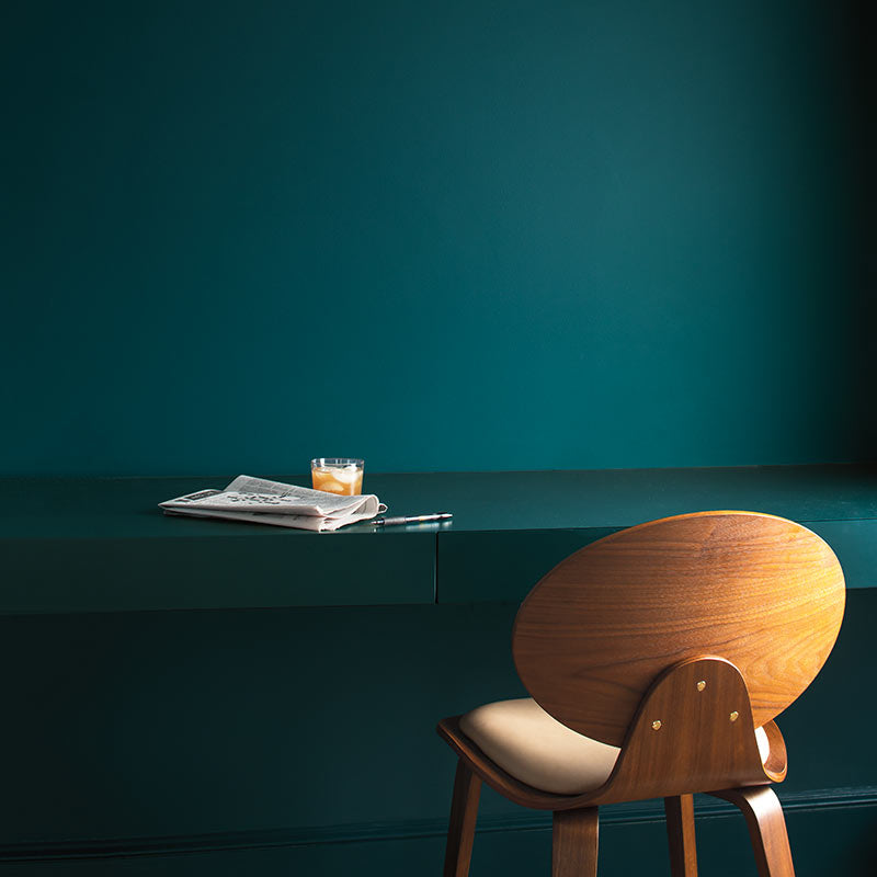 A rich teal wall with painted desk and armless wood chair. Color of the Year 2019