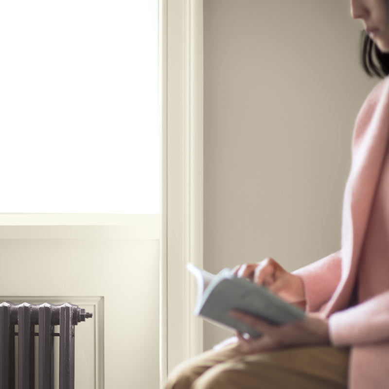 A woman sits reading next to a window with white trim and gray-beige-painted wall. Color of the Year 2019