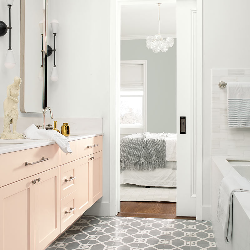 A white-painted bathroom with pale pink cabinets opens to a gray bedroom with contemporary chandelier. Color of the Year 2019