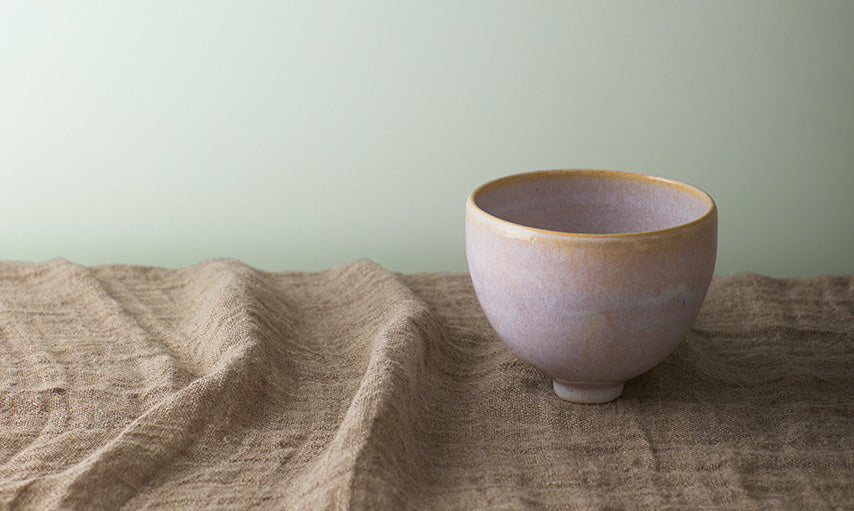 A clay bowl on a countertop in front of a wall painted in Gray Cashmere 2138-60.