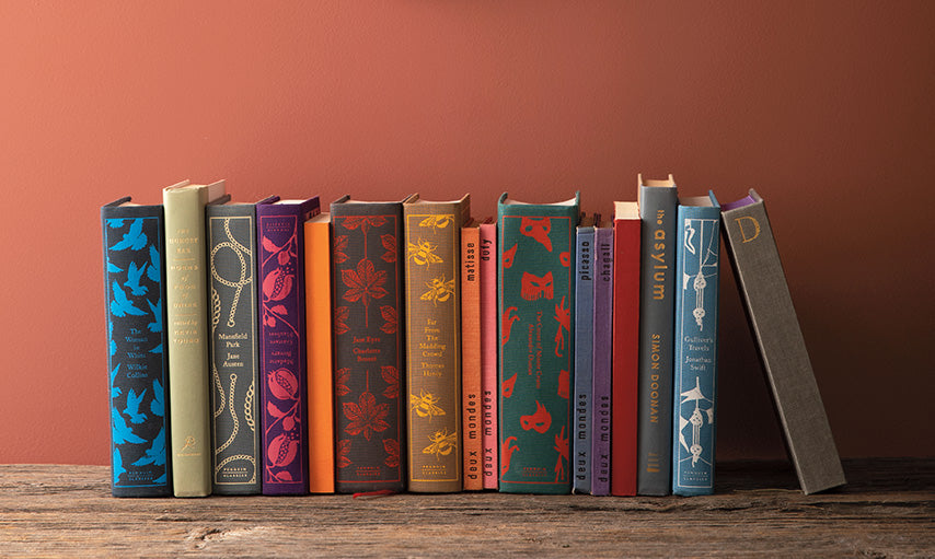 Books on a shelf under a hanging mirror, and wall painted in Rosy Peach 2089-20.