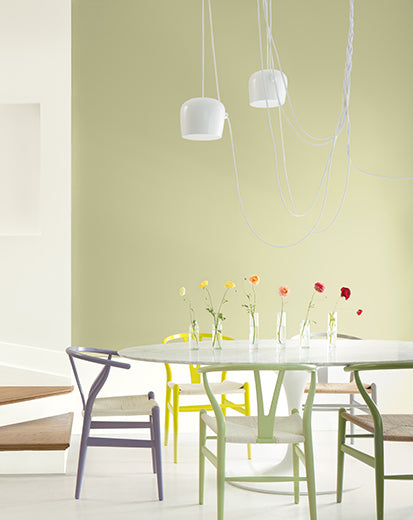 A green-painted dining room with colorful chairs, pendant lighting, contemporary seating and flowers on the table.