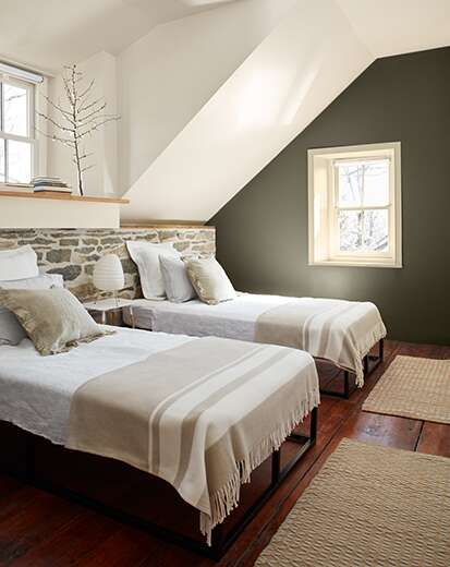 White bedroom with dark green-painted accent wall, two beds in front of a stone half wall, hardwood floors, and small window.