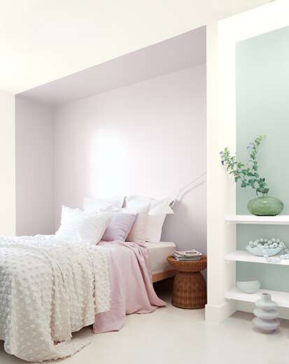 A white bedroom with violet inset and a blue-green accent behind white shelving, bed with white and violet bedding.
