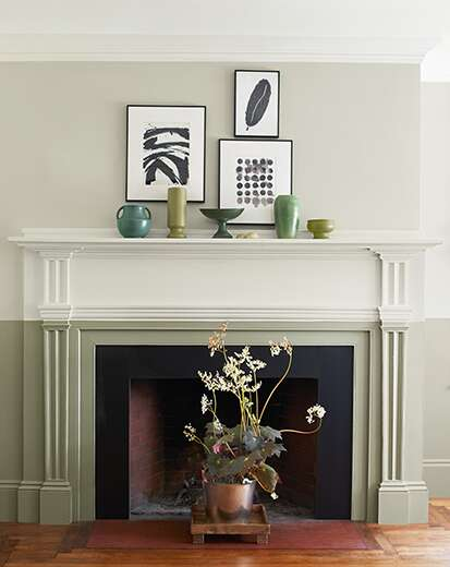 Two-toned fireplace in off white and sage green, with flowering plant in a planter in front of the hearth; art on walls.