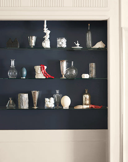 White wall with dark-blue inset shelving and backsplash featuring a variety of décor.