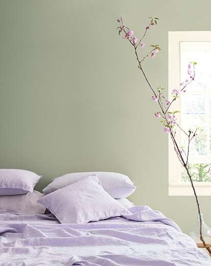 A bedroom with light purple bedding, a sage-green painted wall and flowering indoor tree.