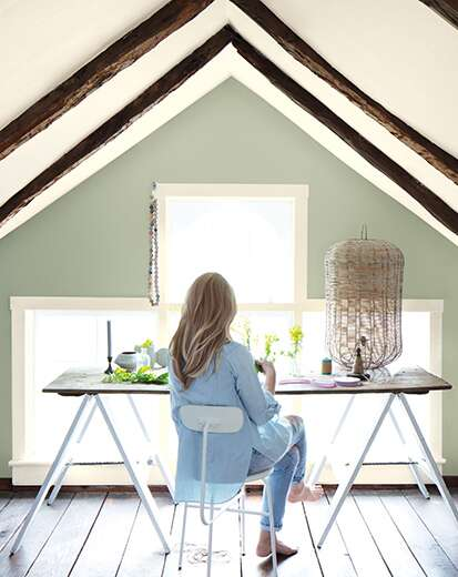 A woman at a desk in a home office with vaulted white ceiling and trim, wooden rafters, large window, and sage-green wall.