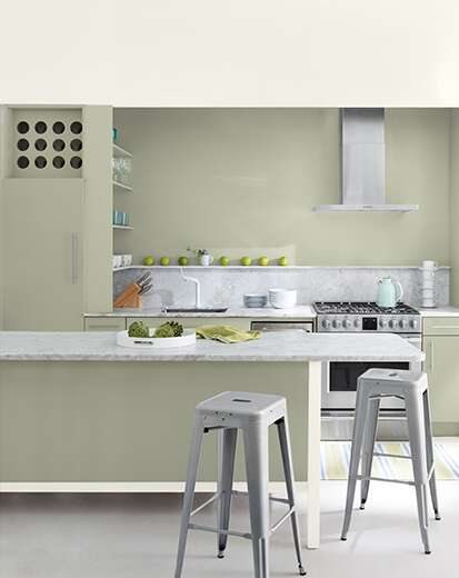 A sage green-painted kitchen with bar seating, silver appliances, and a variety of kitchen utensils.