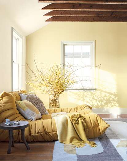 White room with yellow-painted accent wall, wooden rafters, soft yellow chaise, throw pillows, plants, and round end table.