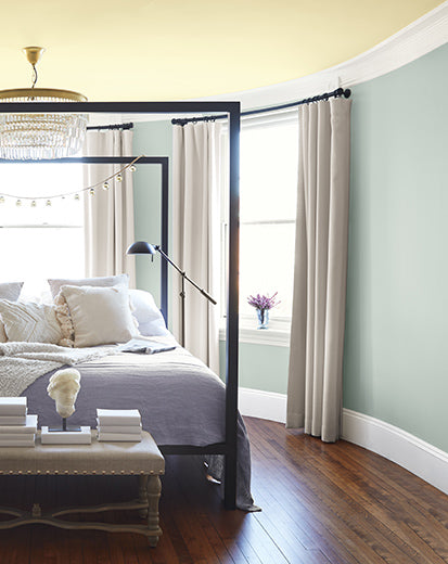 Blue gray-painted bedroom with soft yellow ceiling, large iron-framed bed, small chandelier, and side table with décor.