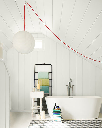 A white-painted bathroom with spherical pendant light, large tub, black shelving, shiplap ceiling, and a white step stool.