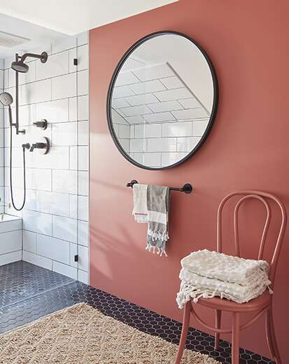 An earthy red-painted bathroom with subway tile shower, round mirror, chair with towels, towel rack, and beige rug.