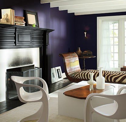 Purple living room with high-end eclectic furnishings and fireplace.