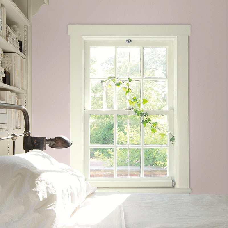 Window-filled bedroom with pink walls and metal-frame bed.