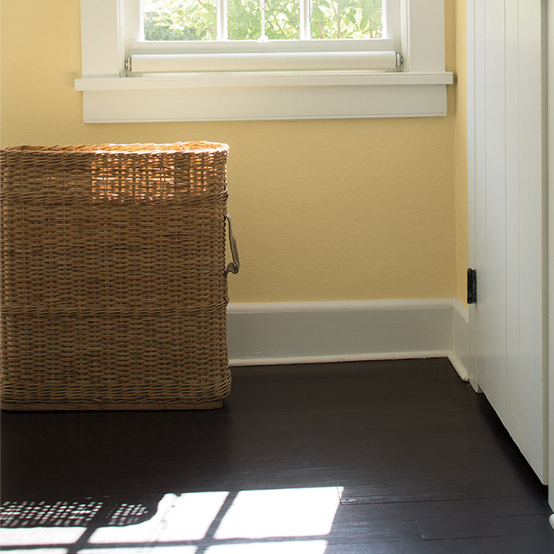 Yellow sunroom with dark hardwood floor wicker basket.