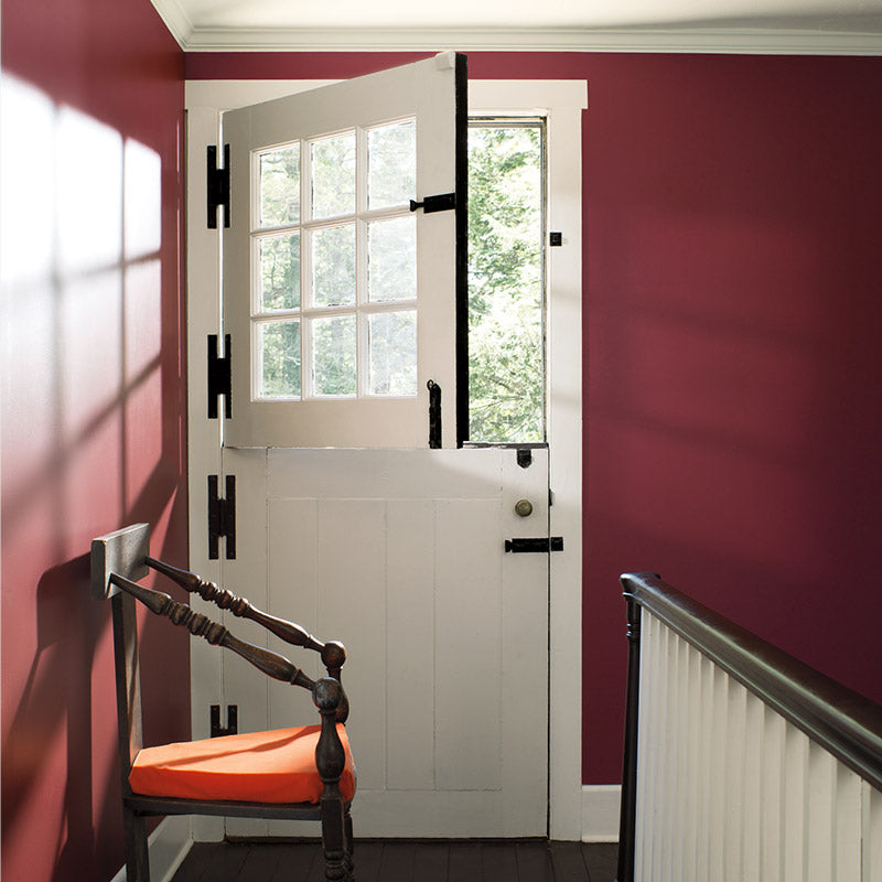 Upstairs landing with banister, rich red wall and farm door.