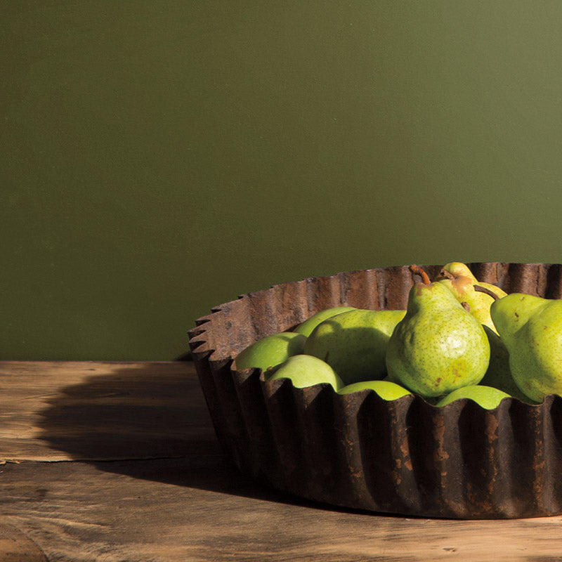 Bowl of pears on a rustic wooden table with olive green wall.