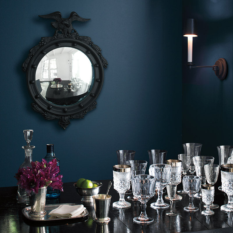 Table with a variety of glasses against a deep blue wall.