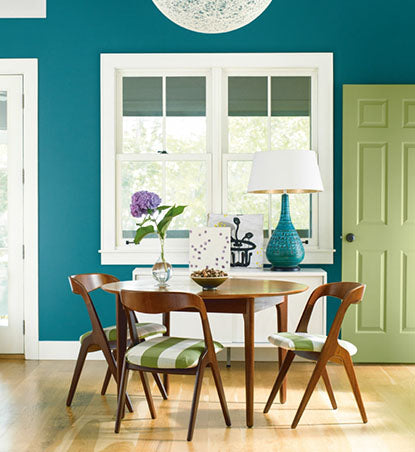 Vibrant green and blue dining room with mid-century table