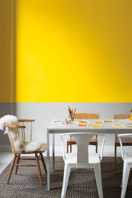Bright yellow and gray dining room with wood and metal furniture