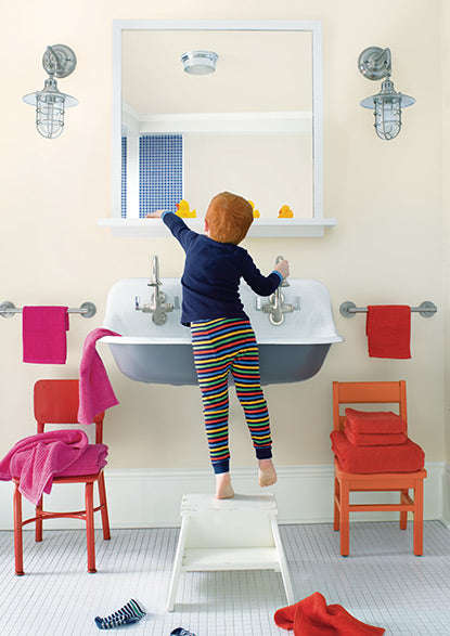 A pale pink bathroom features a little boy conducting his morning routine in front of a farmhouse sink.