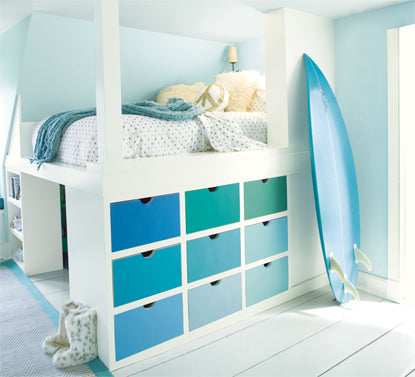 A kid's room with light blue-painted walls features a multi-hued bureau and surfboard.