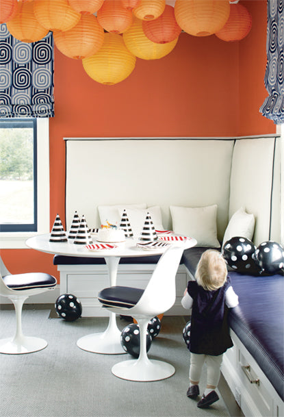 Orange-painted walls and paper lanterns surround a table with birthday hats.