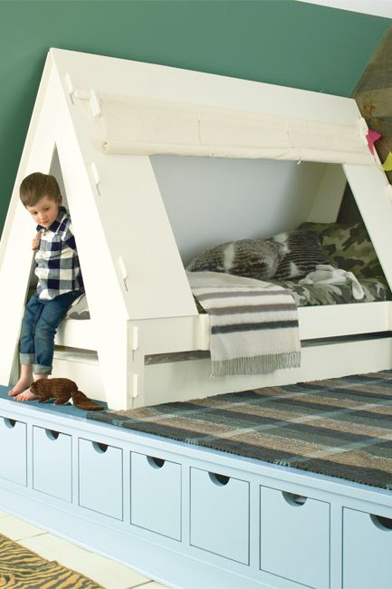 A green-painted angled wall frames a platform with a little boy and his tent bed.