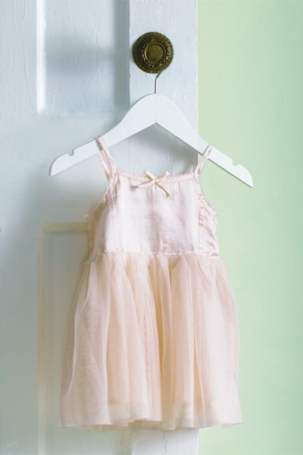 A pale green-painted wall frames a toddler's tutu.
