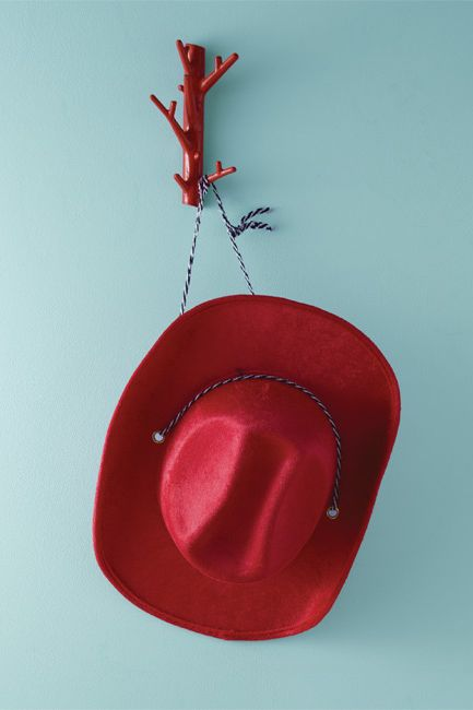 A pale blue wall frames a red cowboy hat.