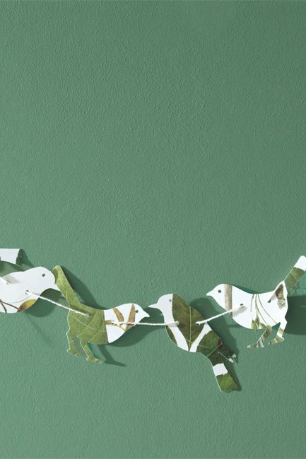 A light green-painted wall is backdrop for an origami banner.