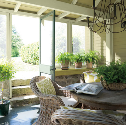 Refreshing greens and yellows flood an enclosed rustic deck.