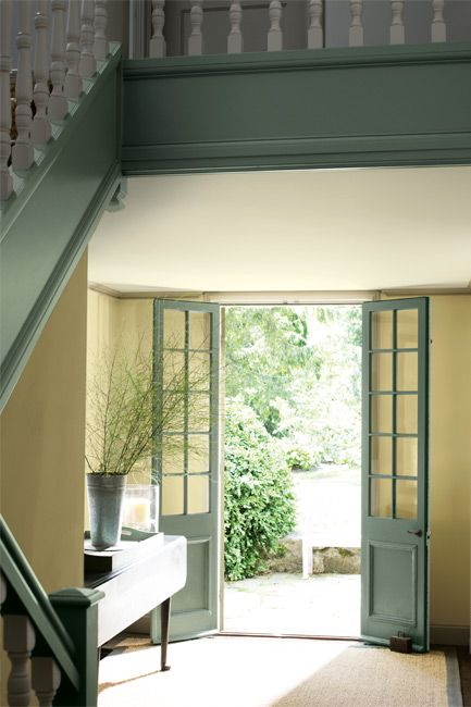 Sunlight floods into a wide entryway through narrow French doors.