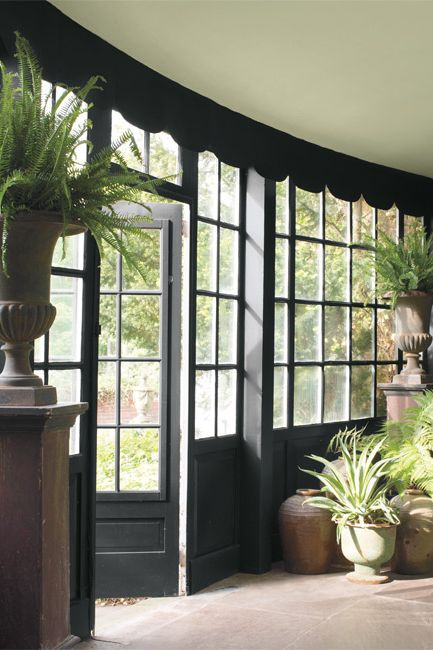 A residential interior features dramatic windows and doors accented by flora-filled urns.