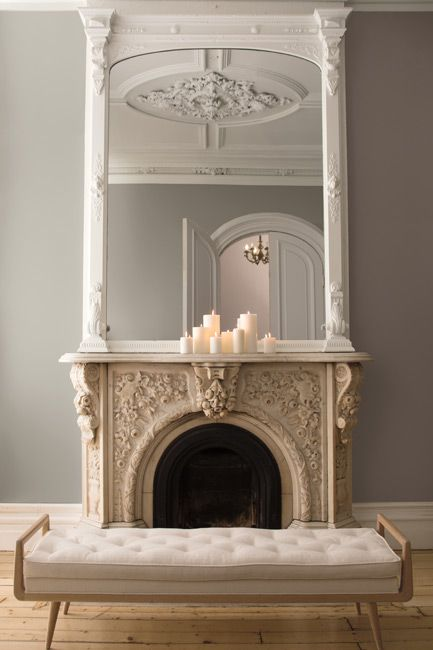 An ornate mirror sits on the mantle of a carved marble fireplace in a calming, neutral-toned room.