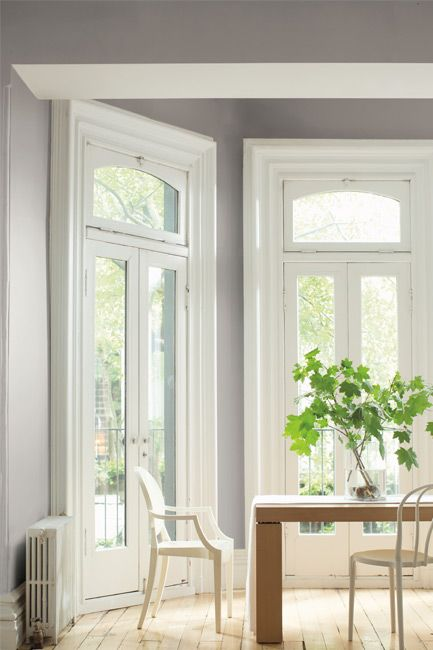 A dining room with modern dining table is surrounded by tall French windows.