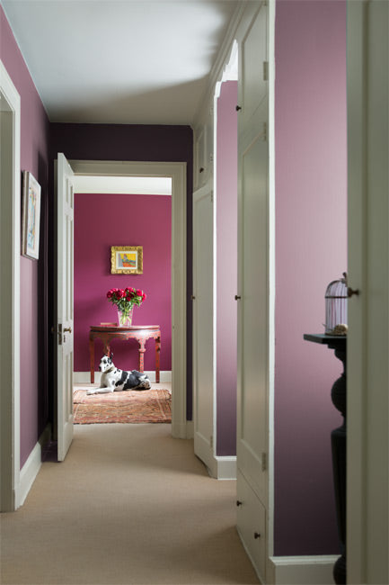 A berry-toned hallway leads to a wood console table topped with pink flowers.