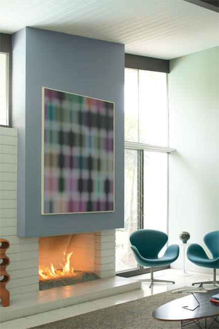 Above a lit fireplace, a light blue accent wall features a colorful piece of modern art.