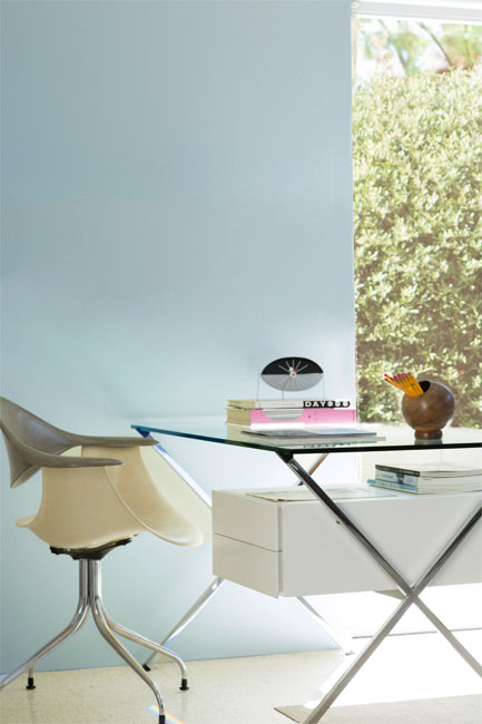 A sleek modern desk and chair are complemented by a light blue accent wall and greenery-filled window.