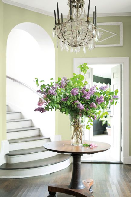 A curved staircase leads into an elegant entryway featuring an ornate chandelier over a round table with flowers.