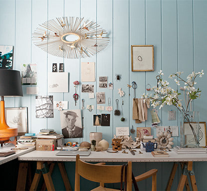 An eclectic selection of momentos, art and reminders are pinned against a light blue, wood-paneled wall over a sawhorse table.