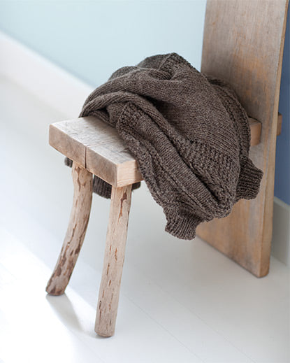 A rustic wood chair with a brown sweater casually tossed across its seat stands out against a white floor and light blue wall.