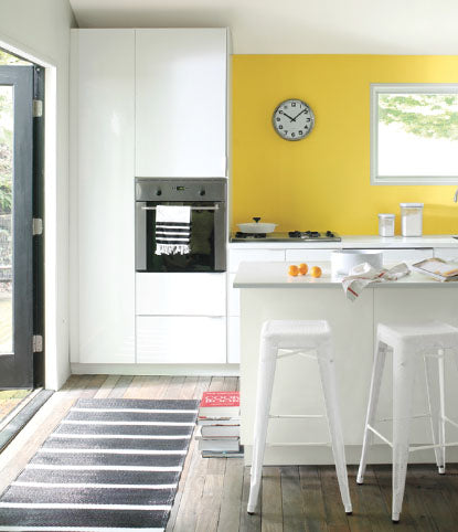Trendy kitchen with yellow wall and industrial chairs.