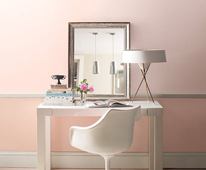 White desk along pink accent wall.