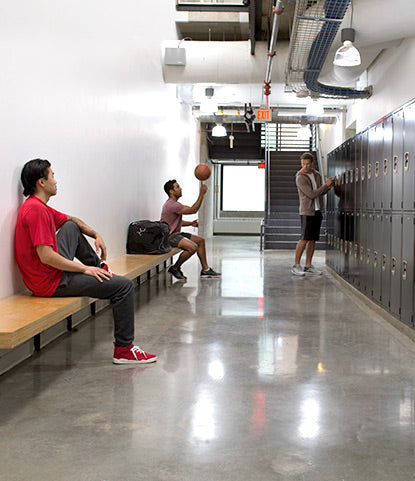 Athletes gather in a crisp, clean locker room, an example of what SCUFF-X can do for spaces that typically scuff and stain.