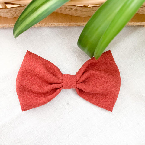 A rust coloured bow clip for babies and toddlers. Locally handmade