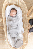 A baby swaddled in the gender neutral grey butter blanket from the OVer Company. Handmade in Canada