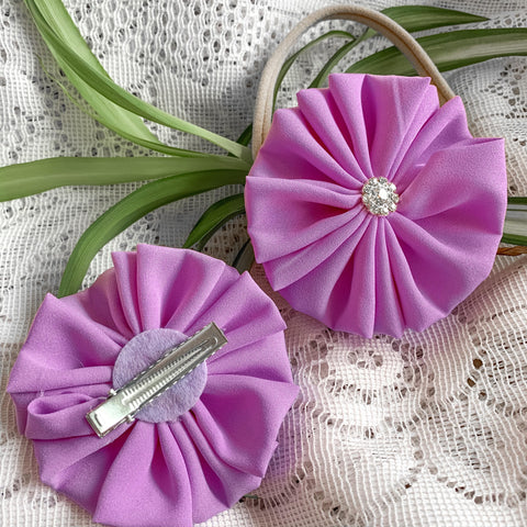 Purple pinwheel bows for babies and toddlers. Gathered purple fabric with a shiny gemstone in the middle.